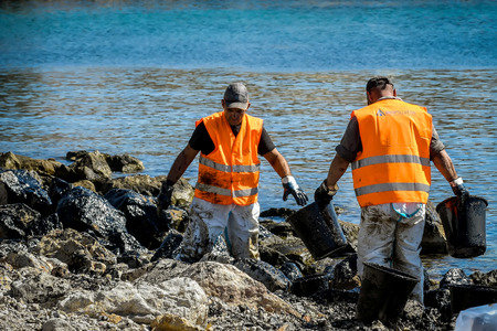 Salamis, Athens, Greece - Sept 13, 2017: Workers try to clean up oil that has washed ashore, on a beach of Salamis island near Athens, after an old tanker sank close to Salamis island Редакционное