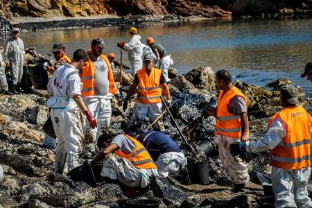 살라 미스, 아테네, 그리스 - 2017 년 9 월 13 일 : 노동자는 오래 된 유조선 Salamis 섬 가까이 침 몰 후 해변, Salamis 섬 해변 근처 씻어 석유를 정리하려고합