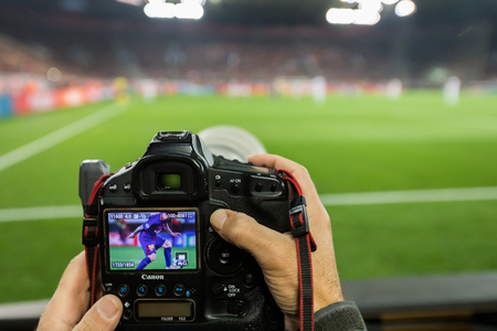 Piraeus, Greece - Oct 31, 2017: hands holding a camera while on display are Lionel Messi during the UEFA Champions League game between Olympiacos vs FC Barcelona at G. Karaiskakis stadium