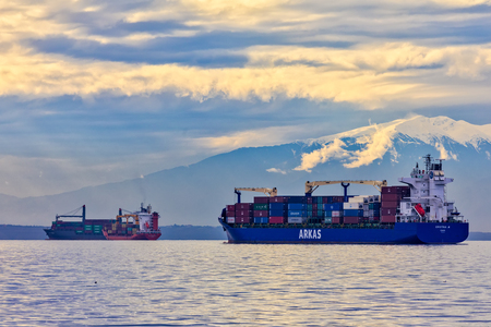 Thessaloniki, Greece - December 4, 2017: The container ship CRISTINA waits anchored close to the port of Thessaloniki for download containers on harbors quay, background snowy mount Olympus Editorial