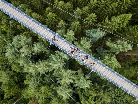 Geierlay, Morsdorf, Germany - July 11, 2017: Holidaymakers cross Germanys longest rope suspension bridge 300 feet above a canyon floor Geierley. It is between the towns of Morsdorf and Sosberg