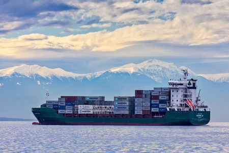 Thessaloniki, Greece - December 4, 2017: The container ship CONTSHIP JOY waits anchored close to the port of Thessaloniki for download containers on harbors quay, background snowy mount Olympus