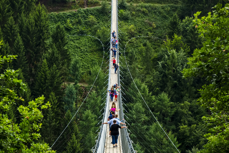 Geierlay, Morsdorf, Germany - July 11, 2017: Holidaymakers cross Germanys longest rope suspension bridge 300 feet above a canyon floor Geierley. It is between the towns of Morsdorf and Sosberg