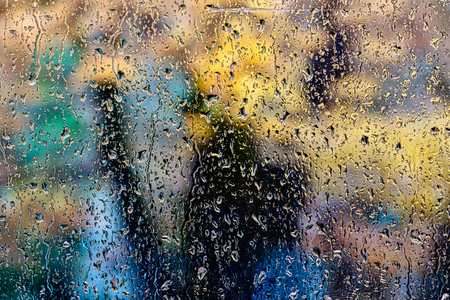 rain in the park glass wet surface with reflection, rain drops on the drenched window glass, background window in the autumn park, autumnal rainy landscape blurred Stock Photo
