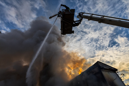 Sindos, Tessaloniki, Greece - December 29, 2017: Firefighters struggle to extinguish the fire that broke out at in a furniture factory in the industrial area of Thessaloniki