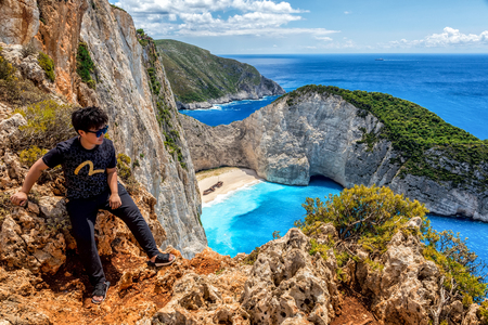 Zakynthos, Greece - July 17, 2017: Travelers on the Background Incredible Navagio (Shipwreck) Beach in Zakynthos island, Greece. Navagio Beach is a popular attraction among tourists visiting the island of Zakynthos