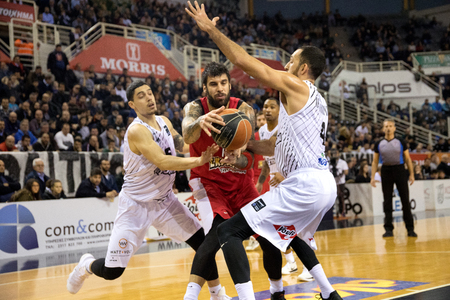 Thessaloniki, Greece, January 7, 2018: Player of Olympiacos Georgios Printezis (C) and player of PAOK Antonis Koniaris (L) in action during the Greek Basket League game Paok vs Olympiacos in Paok Sports Arena Stadium Editorial