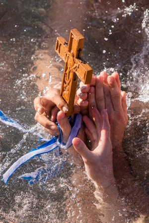 Thessaloniki, January 6, 2018: A close-up shot of the hands that retrieves a wooden cross in the sea, at the blessing of the water ceremony marking the Orthodox Epiphany, at the harbor of Thessaloniki