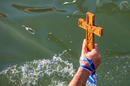 Thessaloniki, January 6, 2018: close-up shot of the hand that retrieves a wooden cross in the sea, at the blessing of the water ceremony marking the Orthodox Epiphany, at the harbor of Thessaloniki