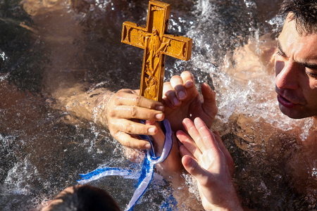 Thessaloniki, Greece, January 6, 2018: A swimmer kisses a wooden cross retrieved from the sea, during the blessing of the water ceremony marking the Orthodox Epiphany Day, in port of Thessaloniki Editorial