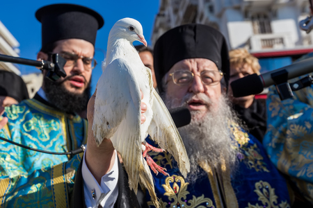 Thessaloniki, Greece, January 6, 2018: Bishop of Thessaloniki Anthimos holds a pigeon, during an Epiphany ceremony to bless the water. This ceremony marks the Epiphany celebrated every year.selective fogus