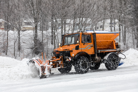 Naousa, Greece - January 13, 2018: Snow-removing machine cleans the street from the snow in the Ski Resort 3-5 pigadia during the snowfall  in northern Greece