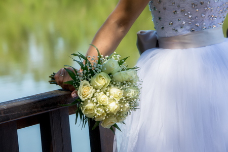 Close view of beautiful wedding bouquet with white roses in a hand of a bride (soft focus). Stock Photo