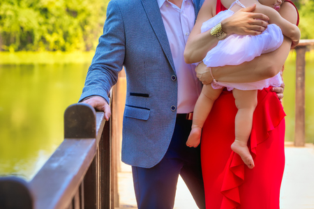 Parents with baby girl standing near lake, close-up, summer (soft focus). Standard-Bild
