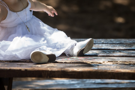 Child feet in shoes on a dark wood