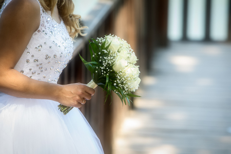 Close view of beautiful wedding bouquet with white roses in a hand of a bride (soft focus). Standard-Bild