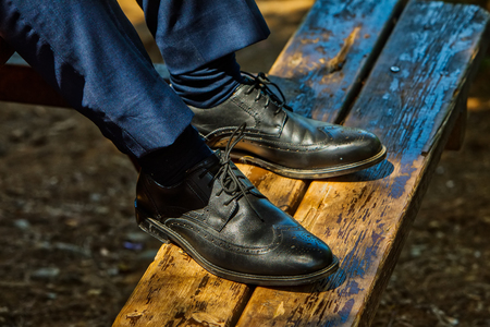 Close-up of a mans leg sitting at the top of the wooden bench relaxing Standard-Bild