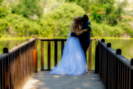 Beautiful wedding couple in park. They hug each other (soft focus).