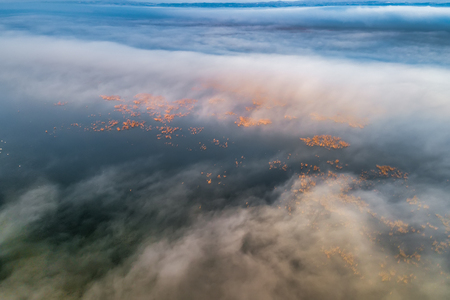 Aerial View. Flying over the clouds . Aerial camera shot. During the sunset. Landscape panorama. Standard-Bild