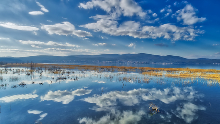 reflection of clouds at the wetland of Lake Doriani on a winter day in northern Greece. atmospheric effect