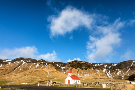 view of typical icelandic church next to a mountains. Standard-Bild