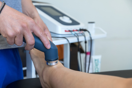 Electro stimulation used to treat pain, muscles injuries, strains and tension in hospital physiotherapy medical rehabilitation clinic for patient knee and leg.