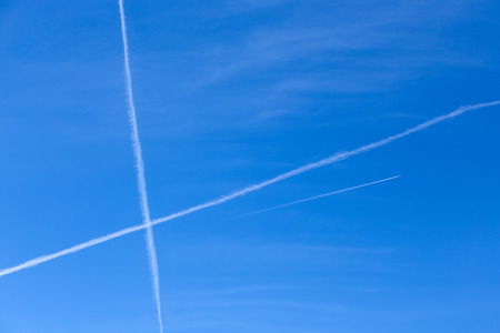 Long white trail in beautiful blue sky from engine flying plane  Stock Photo