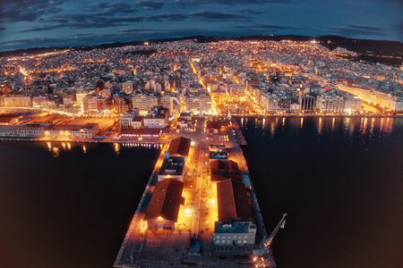 Aerial view of harbor and city Thessaloniki at night, Greece. Image taken with action drone camera causing distortion and blur. Stock Photo