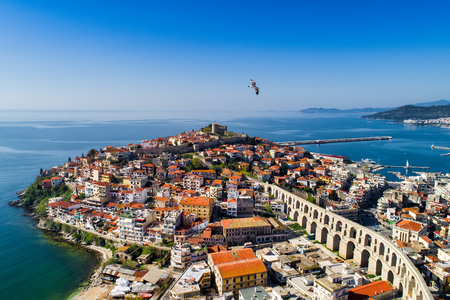 Aerial view the city of Kavala in northern Greek, ancient aqueduct Kamares, homes and medieval city wall  写真素材