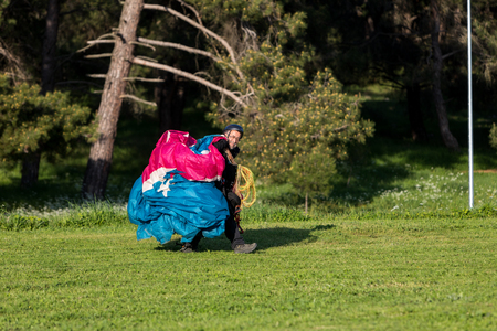 Drama, Greece -  April 8, 2018: Man with a paraglider on a green field after landing waving