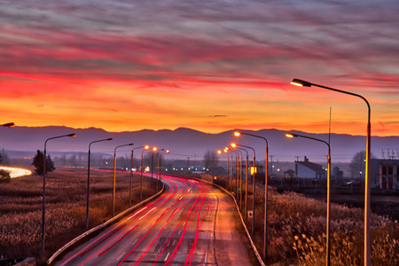 Speed Traffic - light trails on motorway highway at sunset