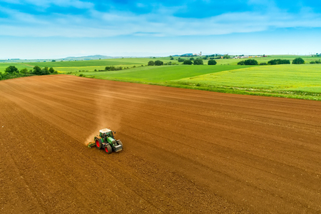 Luchtfoto van boer met een tractor op het landbouwgebied zaaien. trekkers die in het voorjaar op het landbouwgebied werken. Katoenzaad
