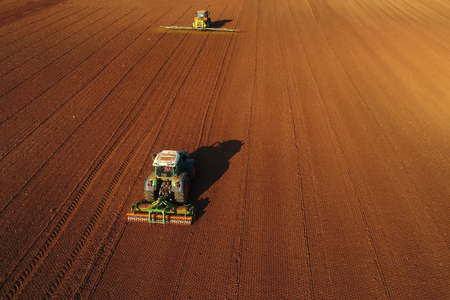 Aerial shot of  Farmer with a tractor on the agricultural field sowing. tractors working on the agricultural field in spring. Cotton seed