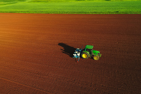 Aerial shot of  Farmer with a tractor on the agricultural field sowing. tractors working on the agricultural field in spring. Cotton seed Stok Fotoğraf - 101038645