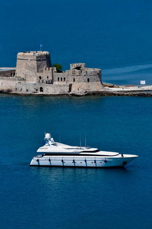 Large private motor yacht at sea in front Bourtzi Castle of Nafplio, Greece