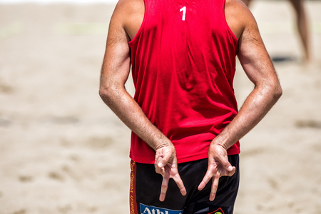 Thessaloniki - Greece June 8, 2018:close up of man buttocks and hands showing beach volleyball hand sign meaning angle attack block during the Hellenic championship Beach Volley Masters 2018 at Aristotelous square