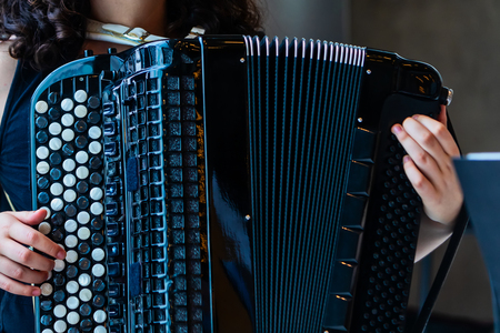 Close-up musician playing the accordion on the stage. Archivio Fotografico