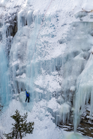 Ice climbing the North Greece, man climbing frozen waterfall.