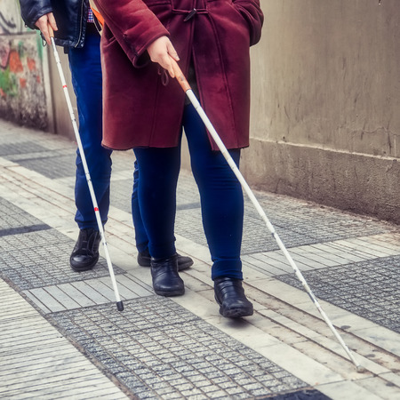 blind man and woman walking on the street using a white walking stick Standard-Bild