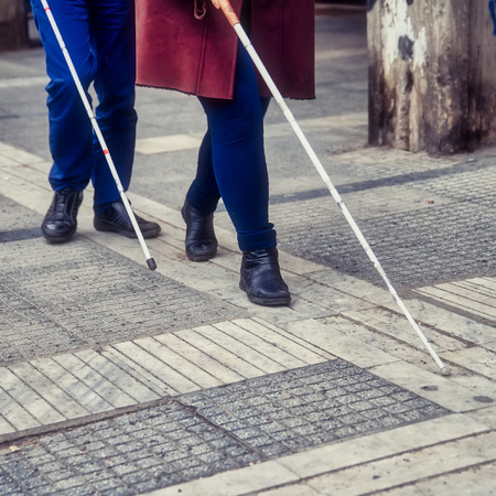 blind man and woman walking on the street using a white walking stick Stock Photo