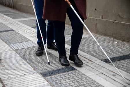 cieco e donna che camminano per strada usando un bastone da passeggio bianco Archivio Fotografico