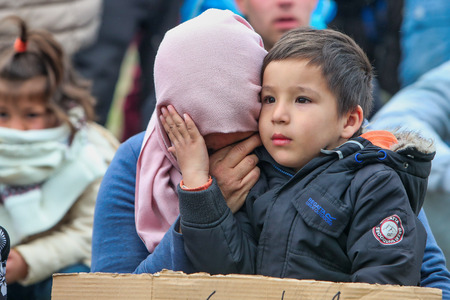 Thessaloniki, Greece - April 6, 2019: The little refugee gives courage to his mother. She just realized that has fallen victim to fake news and can't continue their journey from Greece to Europe.