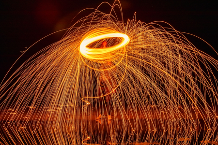 Light painting. Pyrotechnic display at night with the reflection of the water
