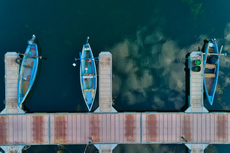 Aerial picture of floating dock with boats, motorboats and vessels floating on water in lake Small Prespes, Northern Greece Archivio Fotografico