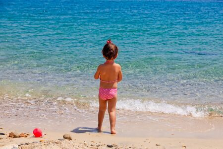 Rear view of a little cute girl is playing on a beach near the sea on vacations. 版權商用圖片