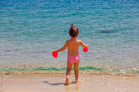 Rear view of a little cute girl is playing on a beach near the sea on vacations. Stok Fotoğraf