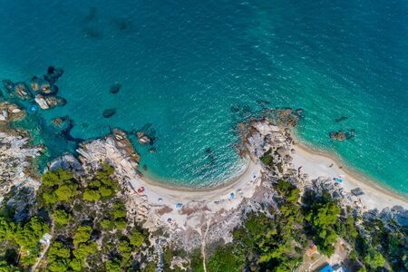 Aerial View of the beach Fava with colorful umbrellas, swimming people in sea in Vourvourou in Chalkidiki, Greece.