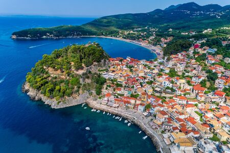 Aerial cityscape view of the coastal city of Parga, Greece during the Summer. Crystal water natural landscape and beautiful architectural buildings near the port of Parga Epirus, Greece, Europe.