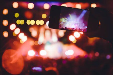 Personas que toman fotografías con teléfonos inteligentes táctiles durante un concierto público de entretenimiento musical. concierto en vivo, festival de música, juventud feliz, fiesta de lujo, paisaje exterior. Enfoque selectivo