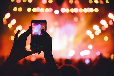 Menschen, die während eines öffentlichen Konzerts mit Musikunterhaltung Fotos mit Touch-Smartphone machen. Live-Konzert, Musikfestival, glückliche Jugend, Luxusparty, Landschaftsäußeres. Selektiver Fokus